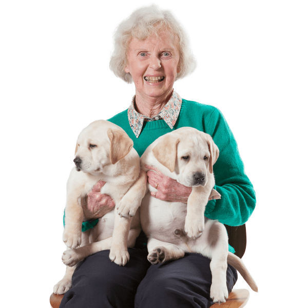 Older woman sitting on chair holding puppies